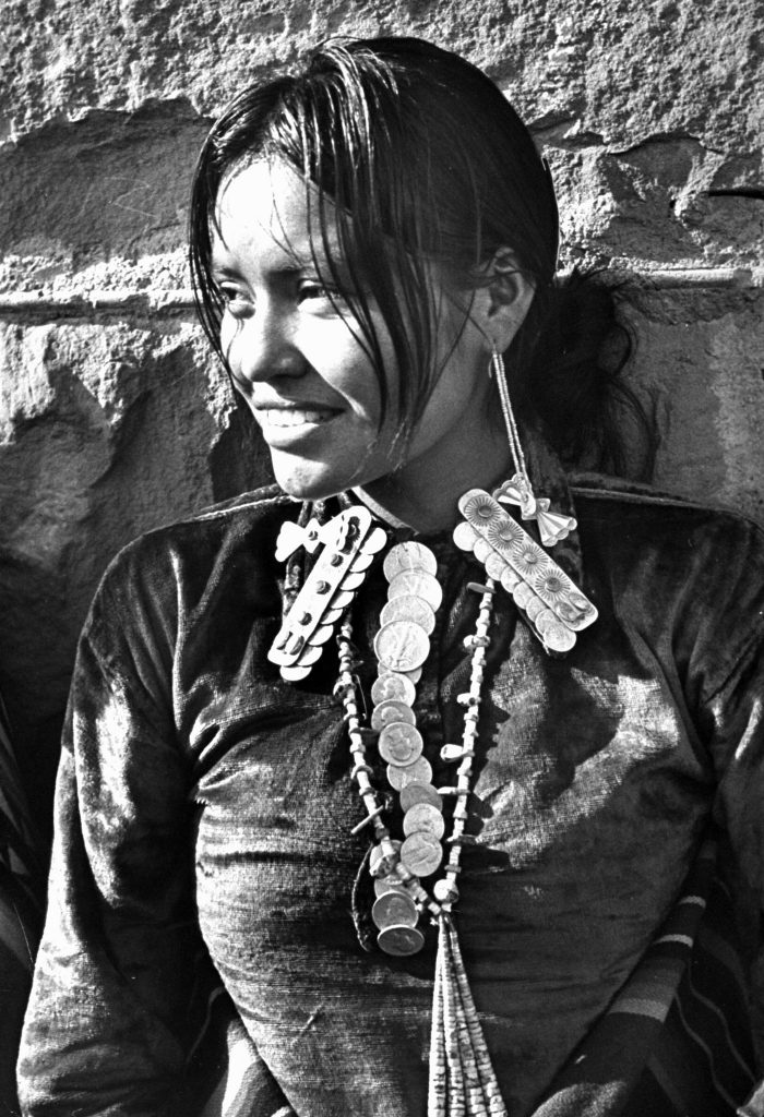 Navajo woman sporting Navajo-crafted silver shirt collar caps, long beaded earrings, beaded necklace complete with silver quarters and 50 cent pieces strung together like a tie.