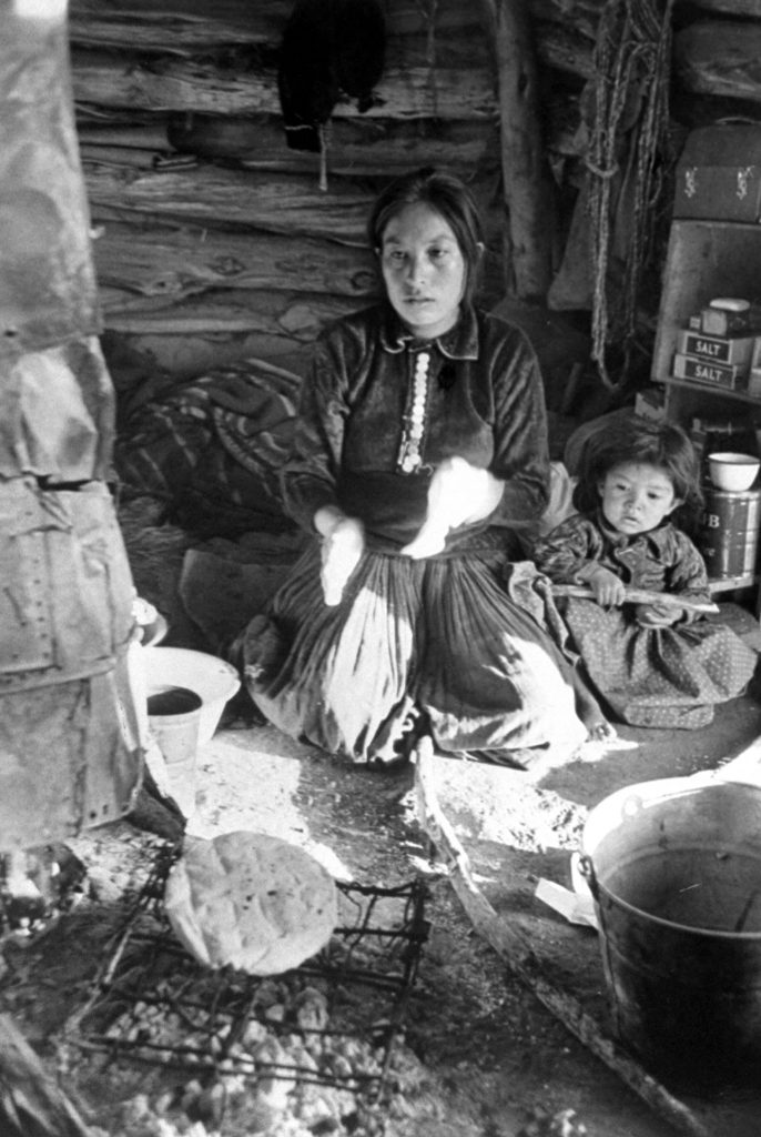 Baking bread, a woman kneels by the fire while loaf cooks on crude metal grill. This native bread is a major item of Navajo diet.