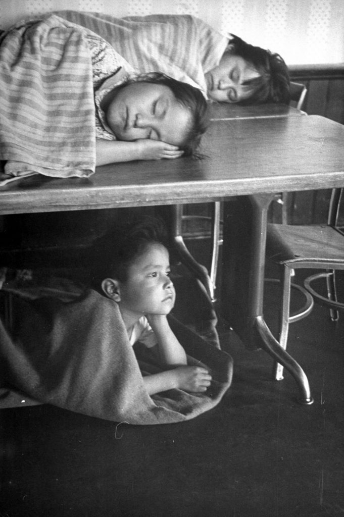 Navajo children taking naps on the tables and the floor.