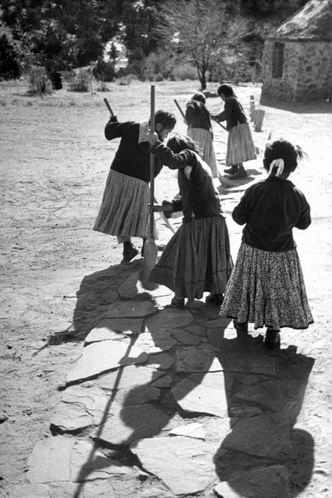 Navajo girls sweeping the sidewalk.