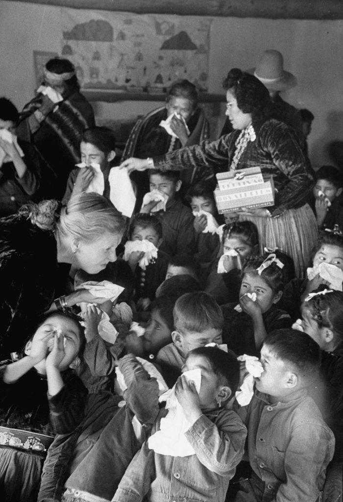 Navajo schoolchildren get a lesson in nose blowing from white teacher.