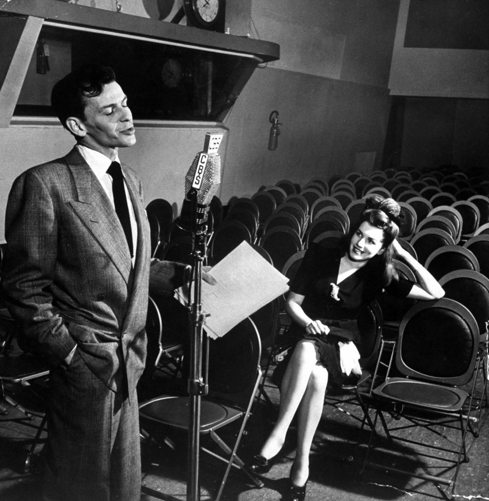 Frank Sinatra singing Close to You in CBS radio broadcasting studio as his admirer Rita Stearns, the winner of the Why I Like Frank Sinatra contest, looks on, in the audience, 1944.