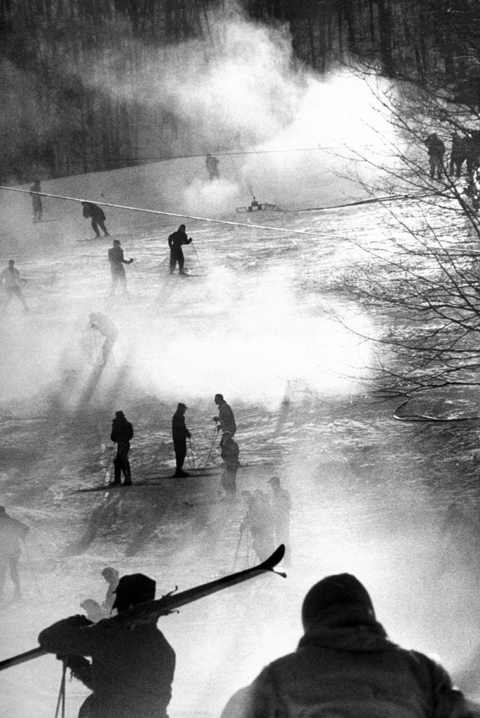 Manufactured snow, blowing from nozzles, veils skiers in mists at Bousquet's, near Pittsfield Mass. During a January thaw, Bousquet's was jammed with skiers unable to ski elsewhere. The artificial powdery surface, made from compressed air and water, can be laid at temperature below 32 degrees.