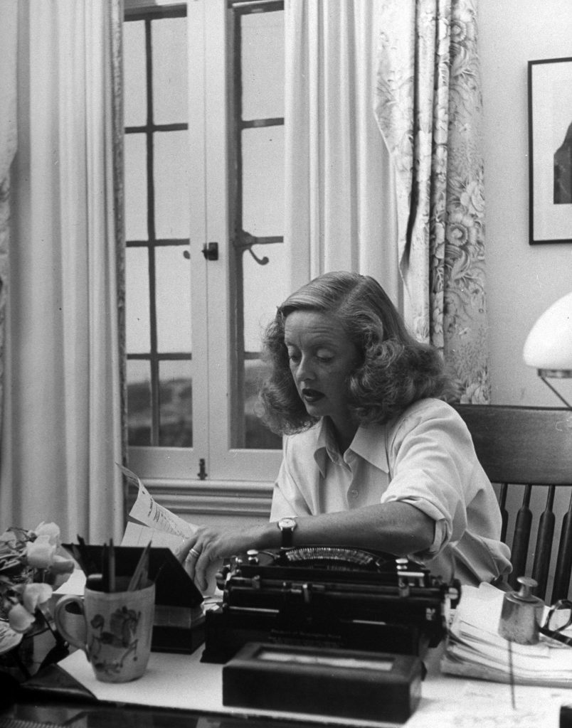 Bette Davis working at her desk at home in California, 1947.