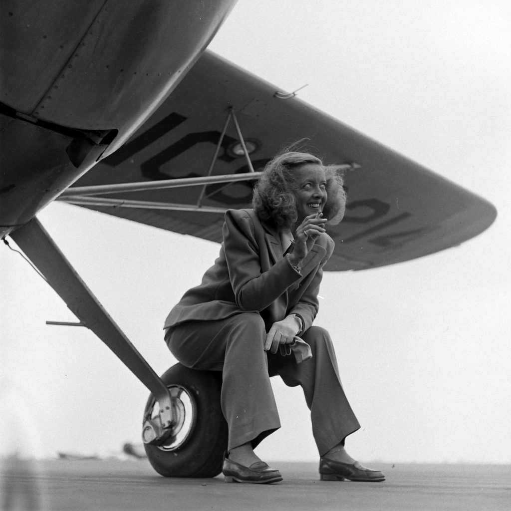 Bette Davis smoking and sitting on the wheel of a plane, 1947.