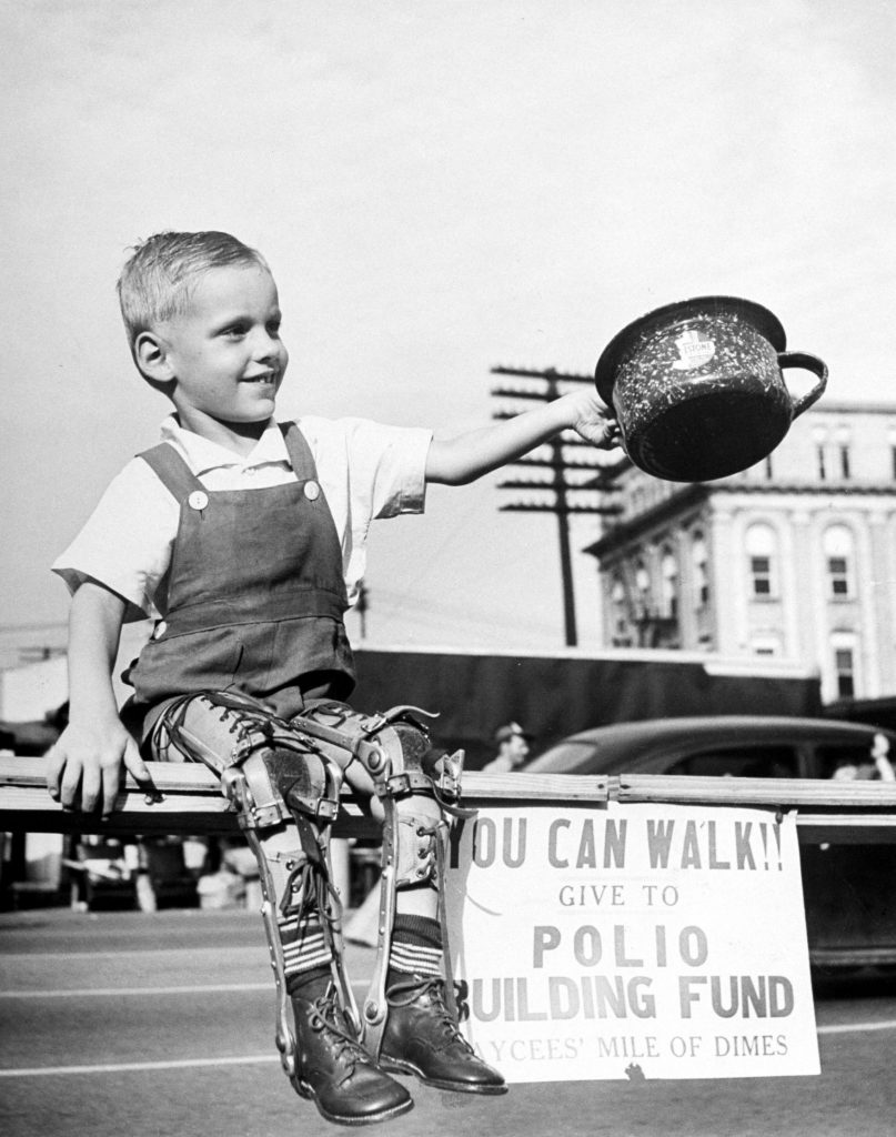 David Henseley, young child crippled by polio with both legs in braces, soliciting funds in public fund-raising driver for a new polio hospital. High Point, N.C., 1948.