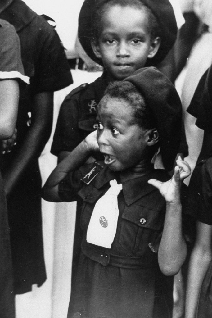A young Jamaican girl scout with surprised look as she watches the arrival of Queen Elizabeth II. Jamaica, 1953.