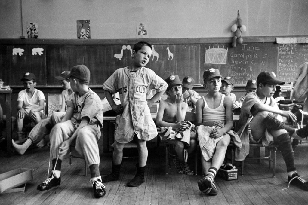 Group of Boys Club little league baseball players putting on their uniforms while sitting in classroom, Manchester, NH, 1954.