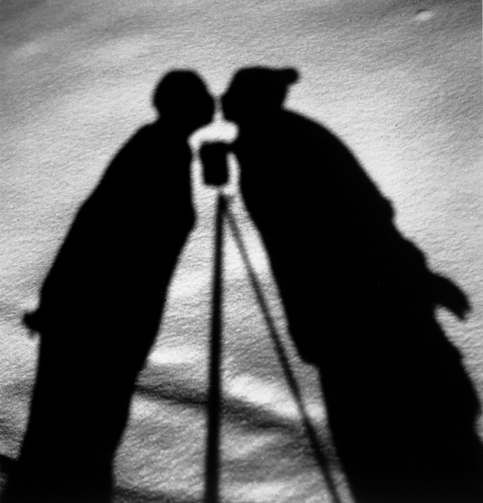 Shadows on the ground of kissing figures with camera on tripod between, 1930.