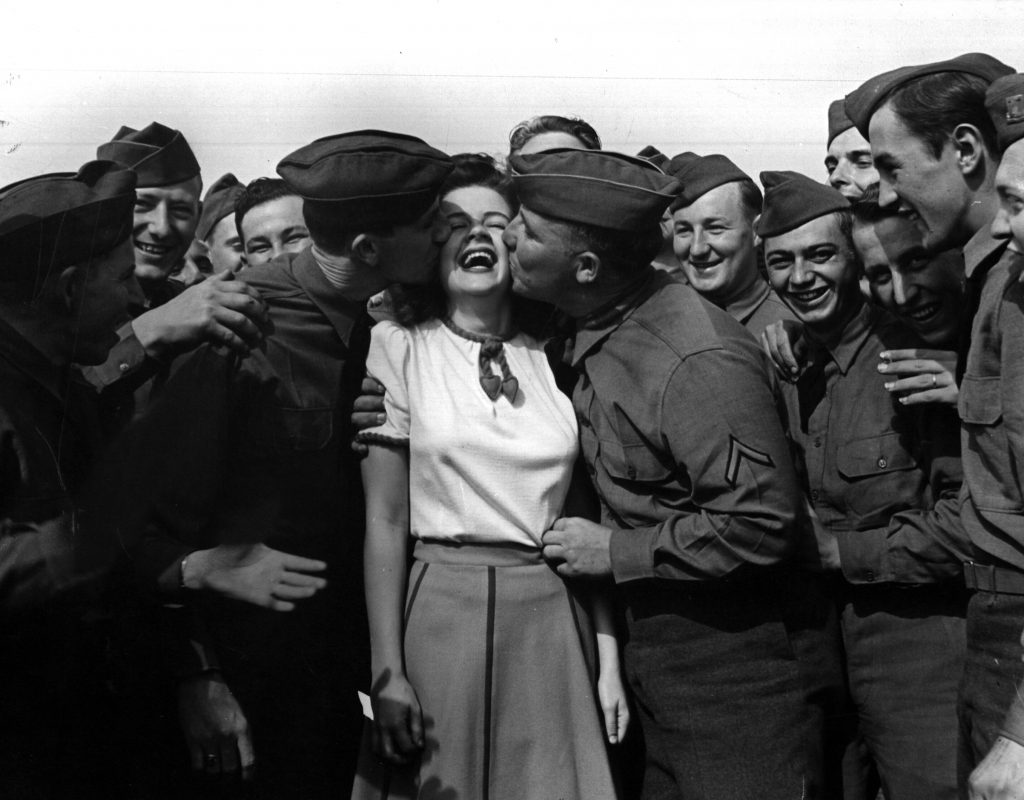 Actress Marilyn Hare being kiss by soldiers as repayment, 1942.