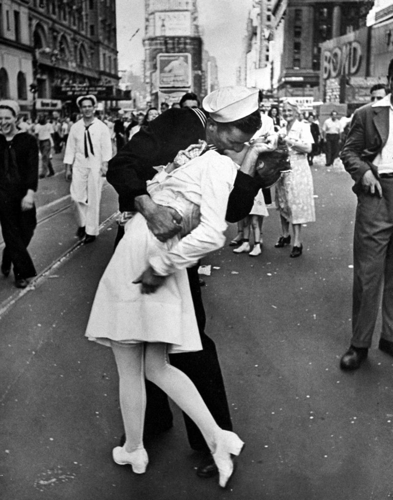 A jubilant American sailor clutching a nurse in a back-bending, passionate kiss as he vents his joy while thousands jam the Times Square area to celebrate the long awaited victory over Japan. 1945.