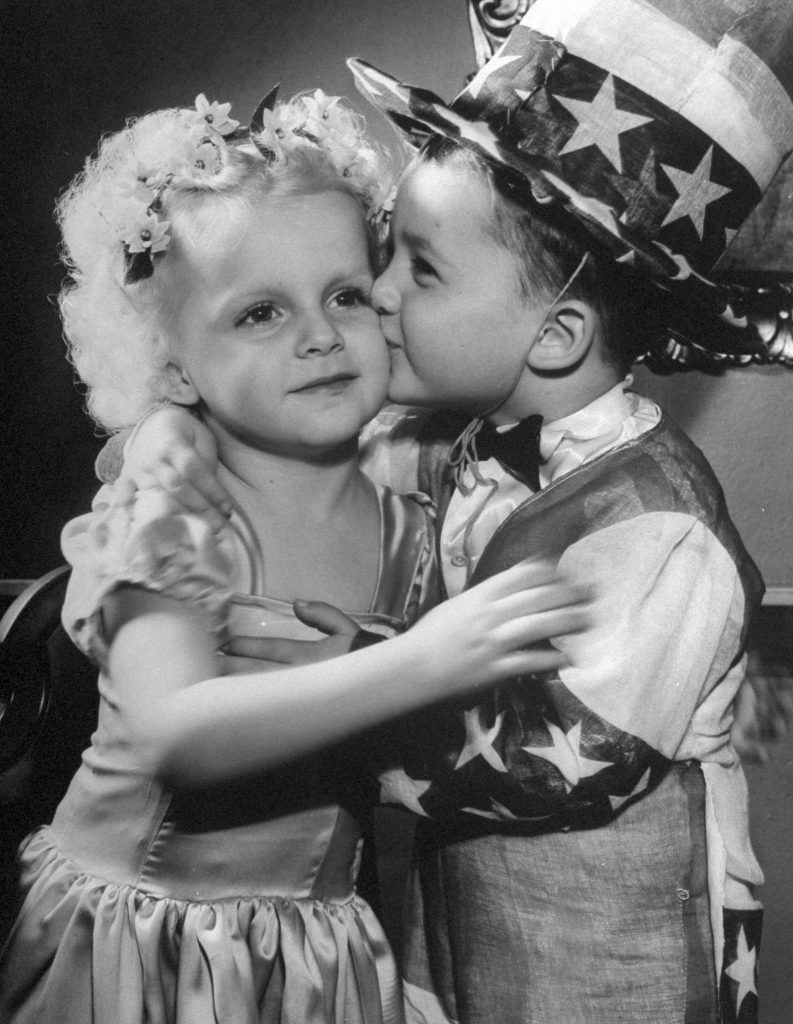 A little boy dressed as Uncle Sam, kissing a little girl on the cheek.1945.