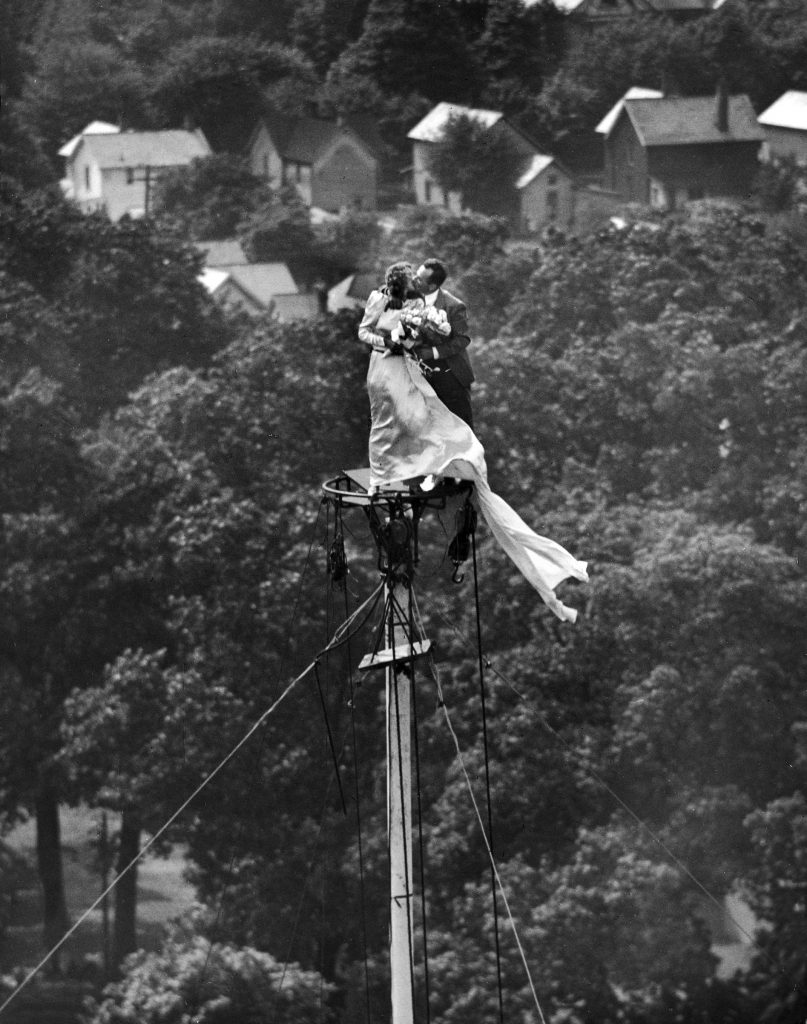 Newly wed couple Marshall Jacobs and wife Yolanda kiss after being married atop a flagpole. 1946.