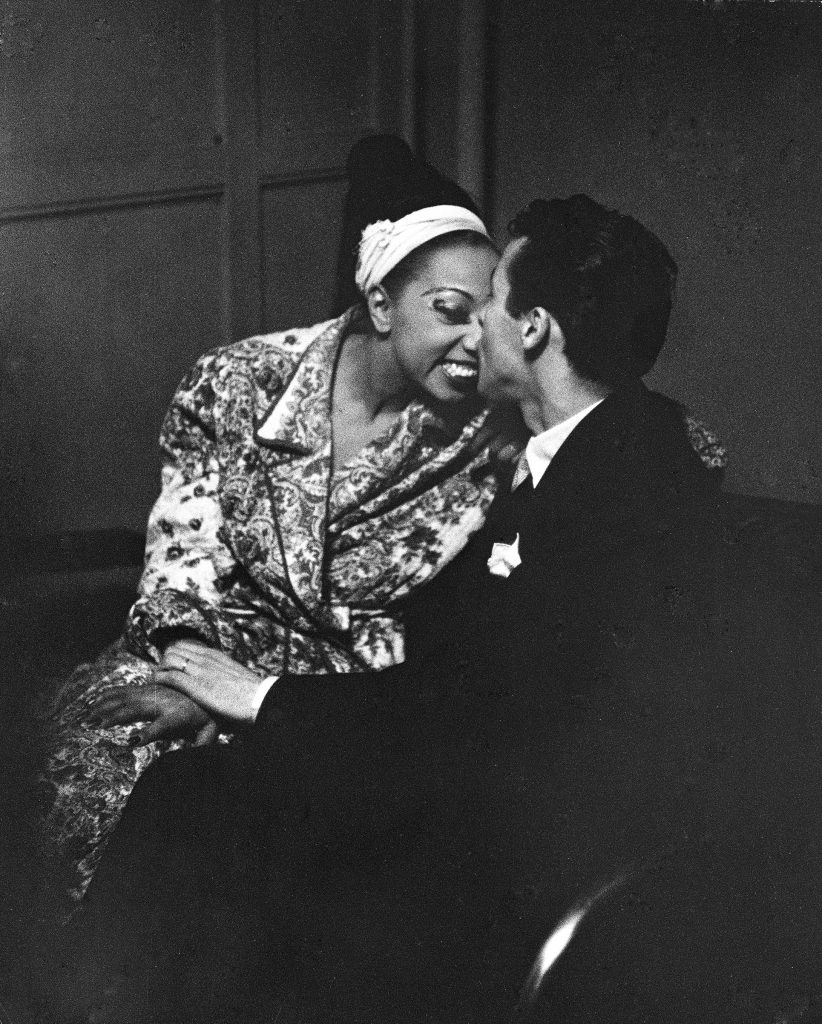 Josephine Baker receiving congratulatory kiss on the nose from her husband, orchestra leader Jo Bouillon, after her show at the Strand theater during her US tour. 1951.
