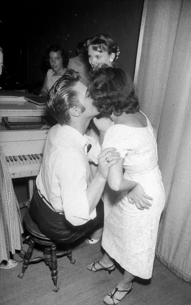 Elvis Presley tenderly embracing and kissing the cheek of a female admirer backstage before his concert, 1956.