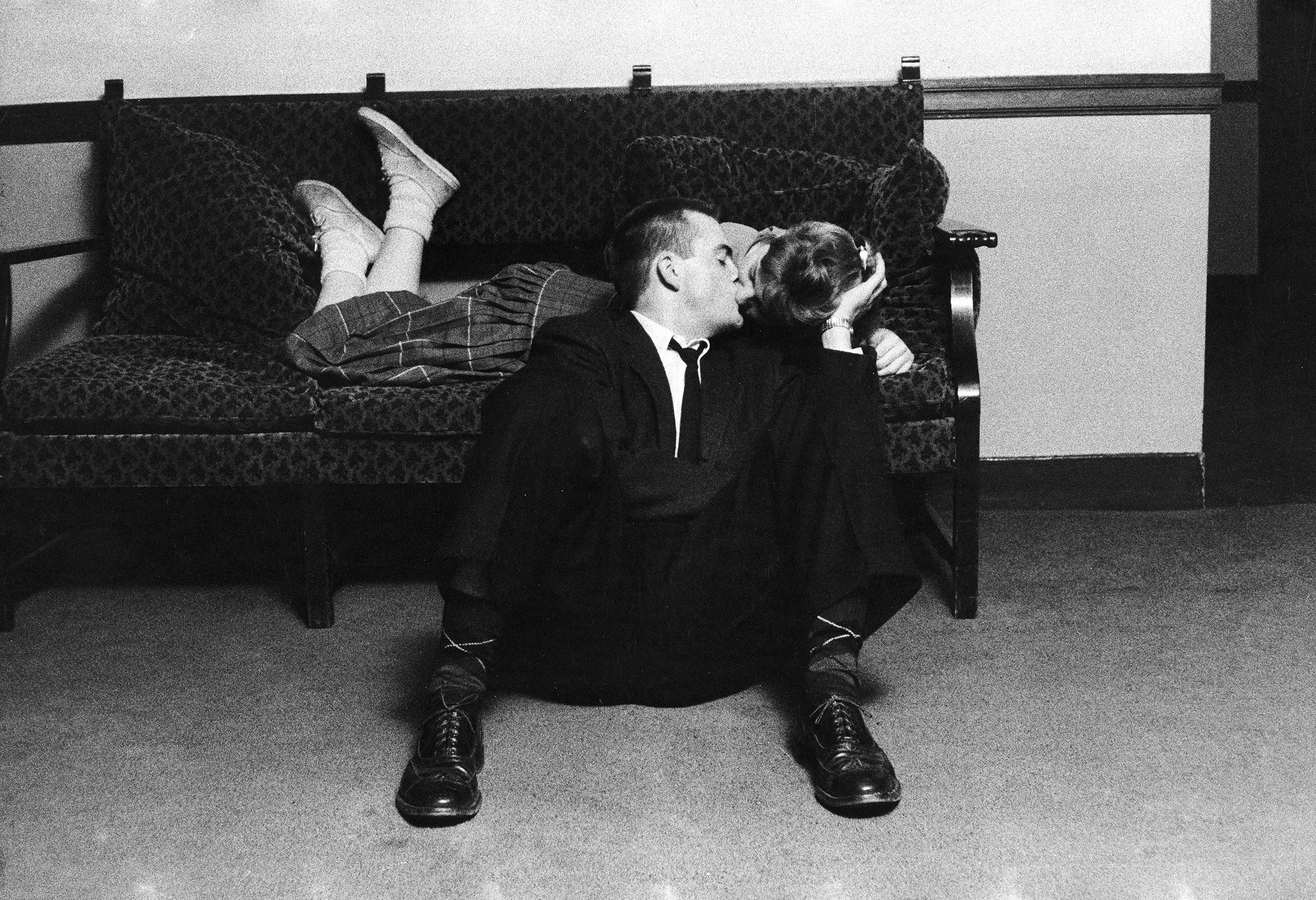 University of Michigan student couple engaged in an impromptu kiss, which was forbidden conduct even before school ban, because earlier rules required couples to have both feet on the floor, in the Union Building on campus. 1957.