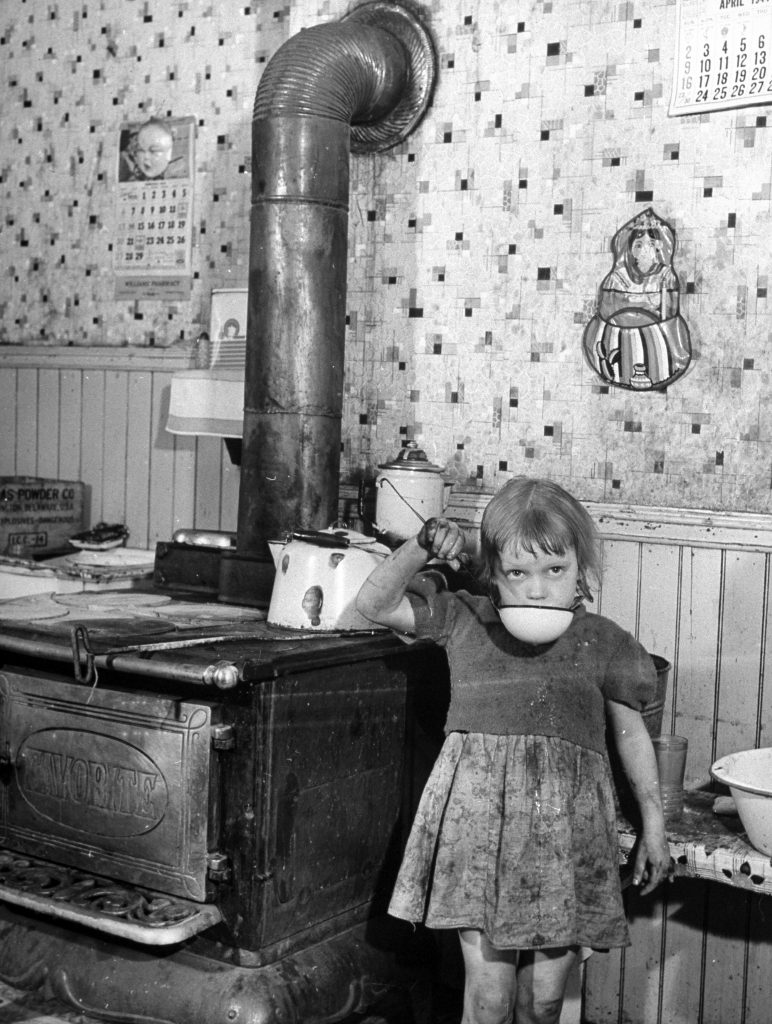 A little girl drinking water in a the dirty kitchen of a steel worker's family in Pittsburgh.