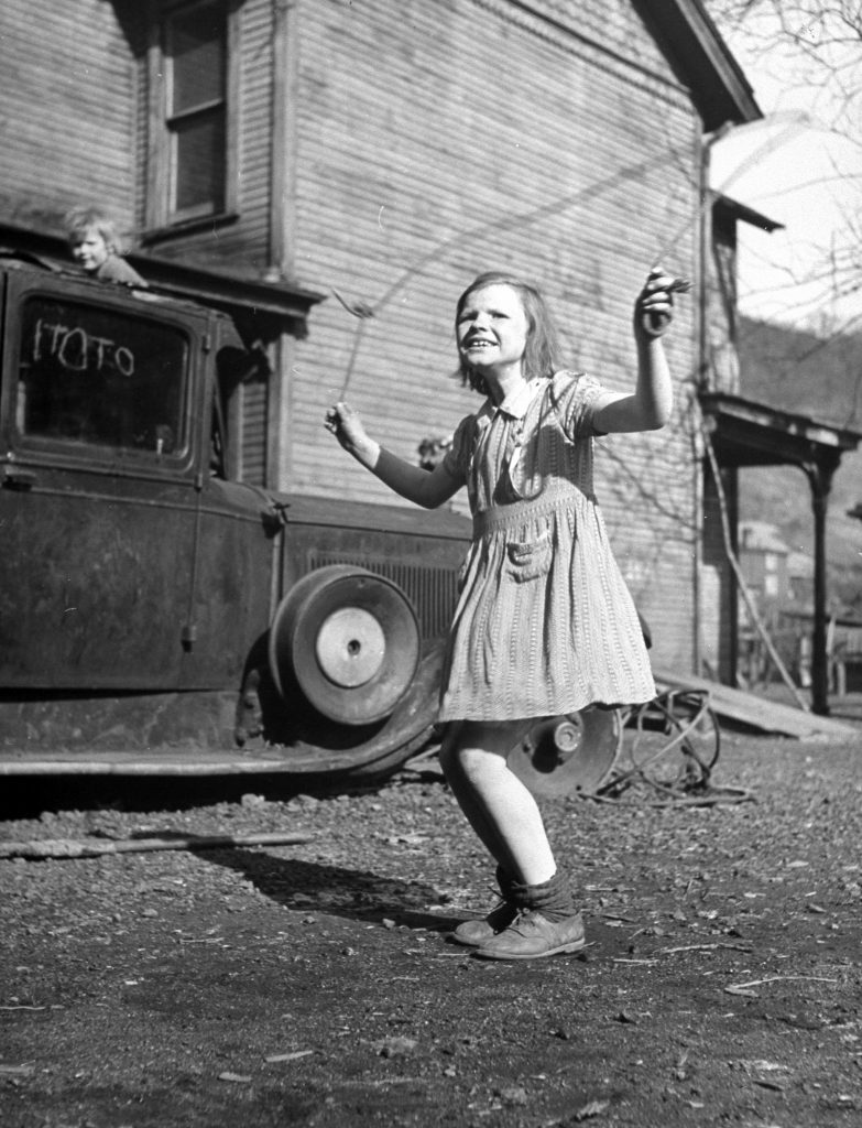 A little girl playing in her front yard in the slum area of Pittsburgh.