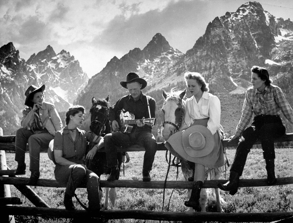 Friends sitting on a fence singing along to the guitar, 1941.