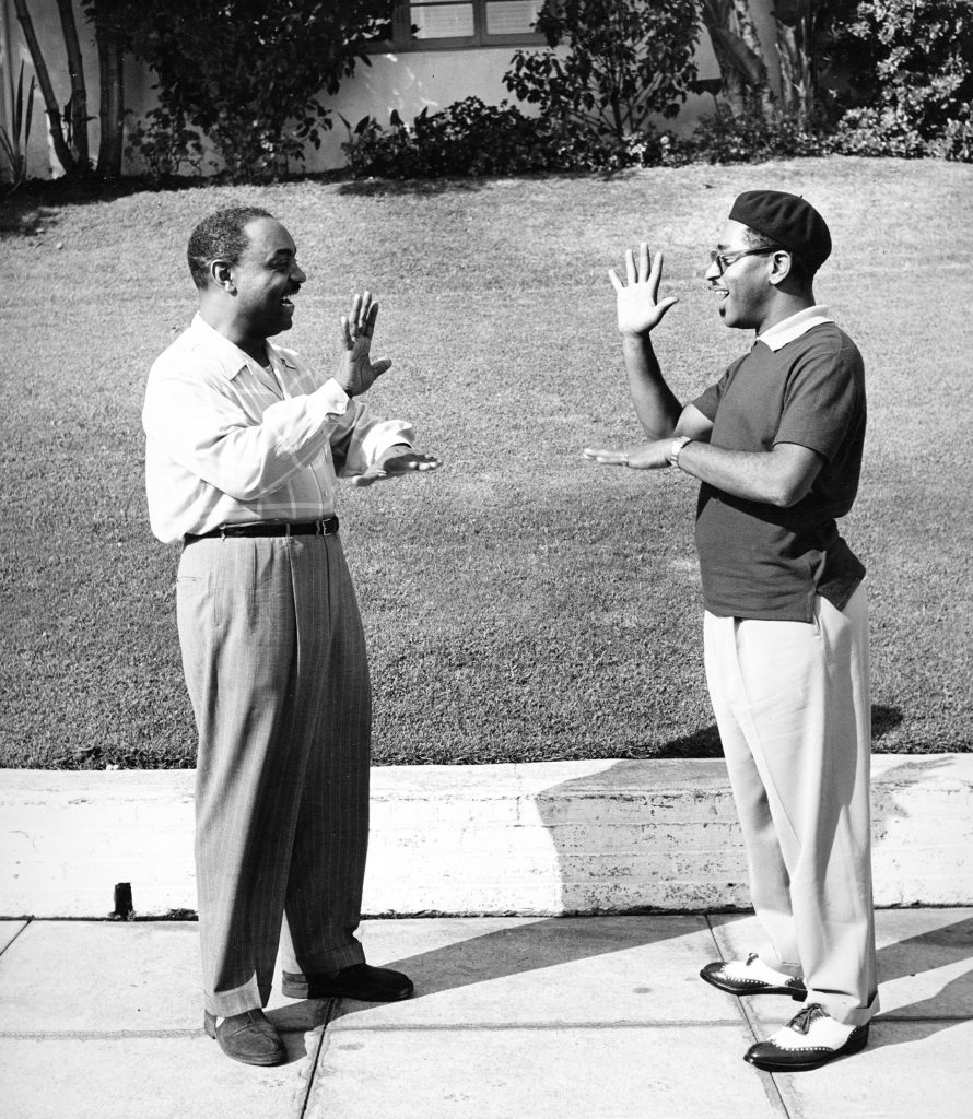 """Bebop"" jazzman Dizzy Gillespie, showing his friend Benny Carter how to do a special handshake greeting, 1947."