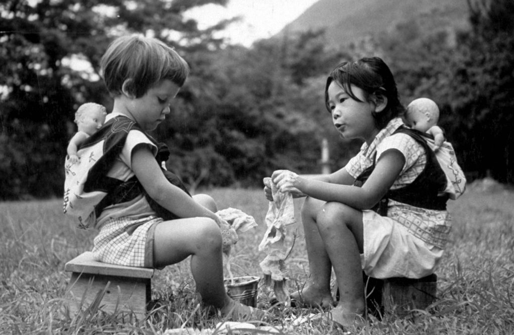 Two young girls playing and washing their doll clothes, 1957.