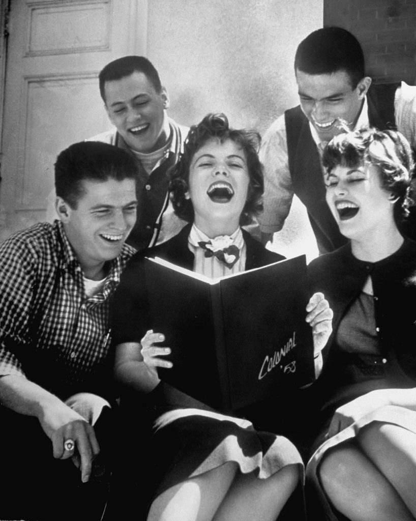 Hempstead High School seniors roaring with laughter as they look over pictures in their newly published yearbook, 1958.
