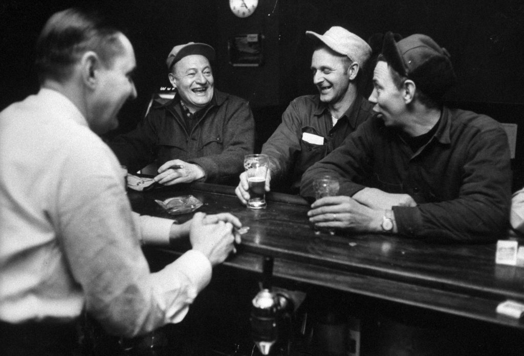 Judge John D. Voelker relaxing with friends in a tavern, 1958.