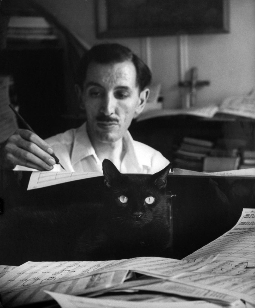 Composer Alan Hovhaness, working in score littered studio with a black cat nestling amongst the papers on the piano, 1955.