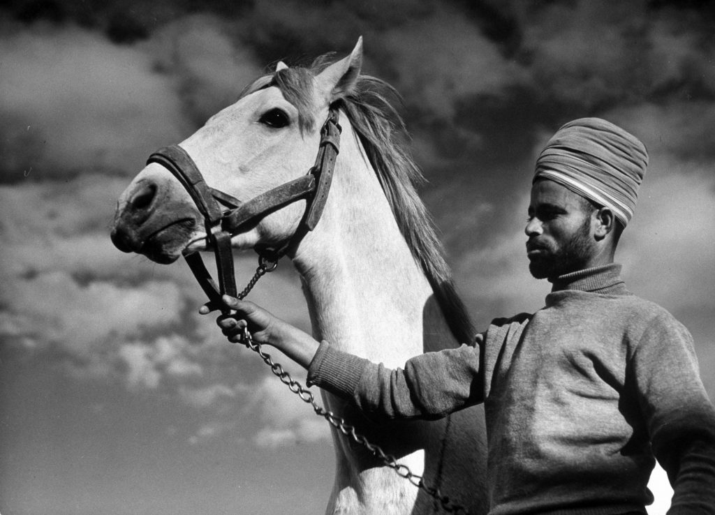 Moroccan soldier of the French expeditionary force, holding the General's Arabian horse, at garrison in the great citadel, 1940.