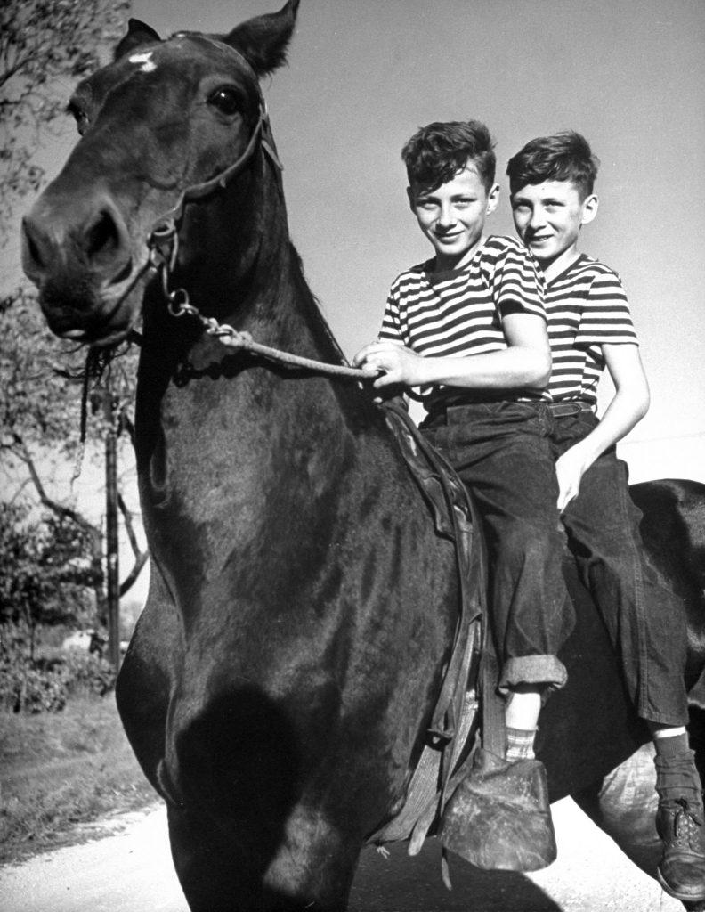 Boys riding a horse to schools, 1946.