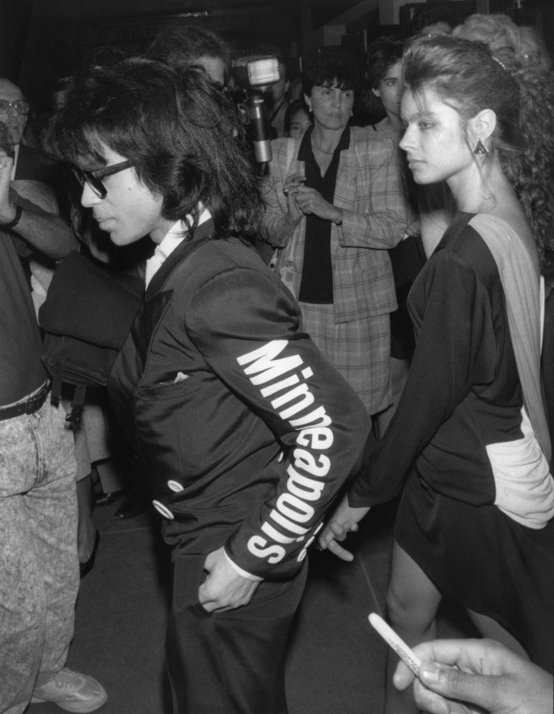 """Musician Prince and an unidentified girlfriend are attending """"M Butterfly"""" on Broadway. He is wearing a jacket with Minneapolis printed on the sleeve which is trademarked for his """"Love Sexy 88 tour"""". New York, NY, September 23, 1988."""